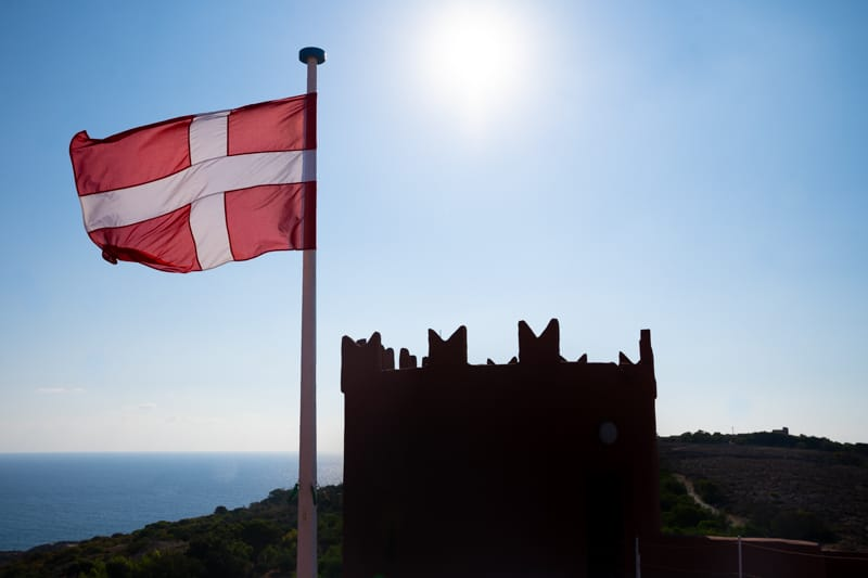 A red flag with a white cross flying above the Red Tower