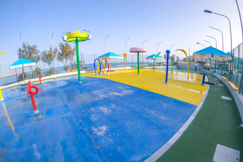 Outdoor water play area with yellow and blue floor and water sprinklers