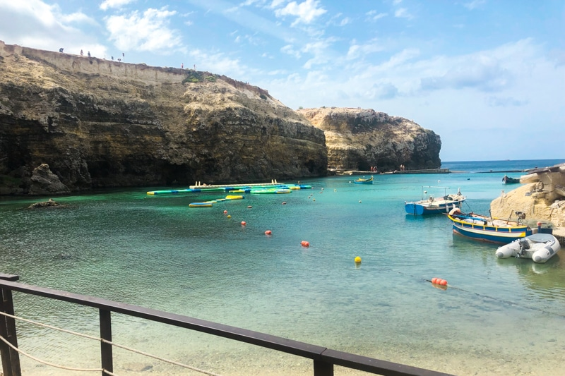 Ocean bay next to cliff with inflatable obstacle course in a water park in Malta